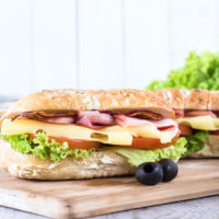 Ciabatta sandwich with bacon and cheese on wooden boarde,selective focus and blank space